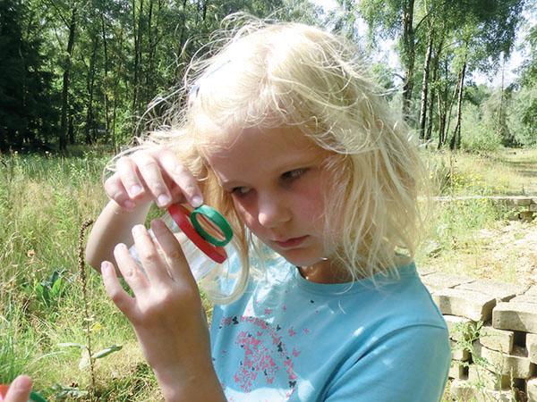 Blondes Kind schaut in Becherlupe