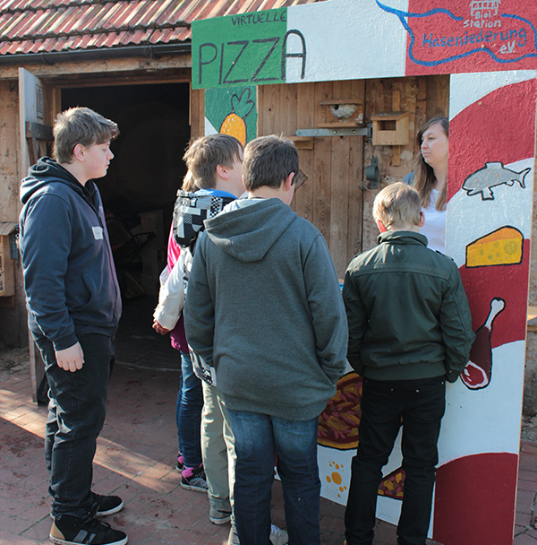 Schüler stehen vor aufgebautem Stand mit virtuellen Lebensmitteln